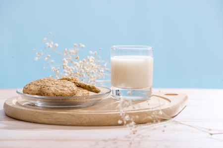 Pastry organic breakfast. Chip cookies and a glass of milk on a white wooden table.