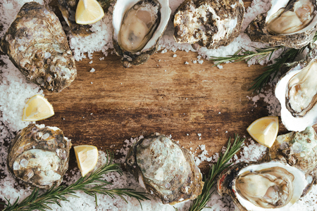 fresh just opened oysters and slice of lemon on rustic wooden background Stok Fotoğraf - 104283528
