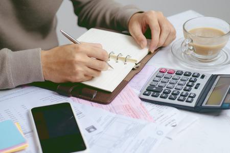 Hombre asiático estresado trabajando a través del papeleo, calculando gastos, tratando de ahorrar algo de dinero, administrando las finanzas, sentado en la mesa de la cocina con la computadora portátil, tratando de hacer un plan financiero Foto de archivo