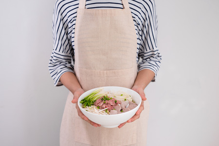 Female chef prepare traditional Vietnamese soup Pho bo with herbs, meat, rice noodles Stok Fotoğraf - 104283636