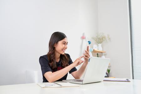 Donna asiatica finanziaria esecutiva che si siede allo scrittorio e che lavora al computer portatile