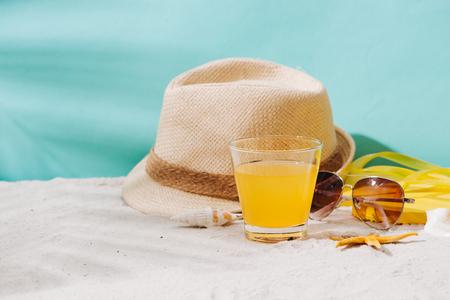 Summer background. Beach accessories flip flops, sunglasses, hat and orange juice on sand background Imagens