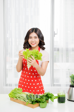 picture of happy woman with lettuce in kitchen Stock Photo