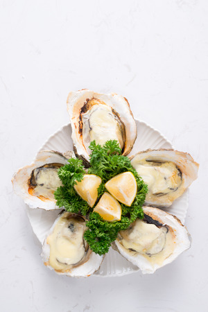 Fresh oysters in a white plate with ice and lemon on a wooden desk Stockfoto