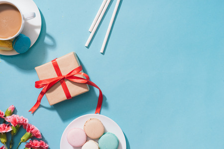 Creative and macarons with gift on blue background. Top view. Flat lay.