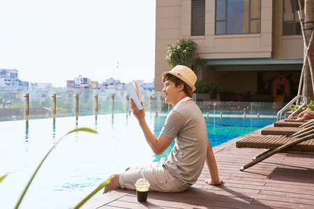 Young asian man reading book by the pool on a sunny summer day Foto de archivo