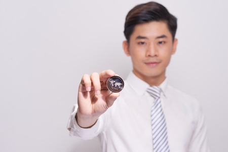 A young business man model holds a bitcoin gold coin Stock Photo
