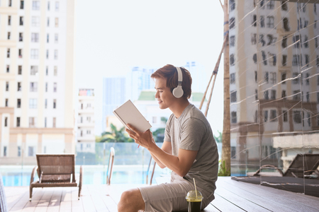 Young asian man reading book and listening to music by the pool on a sunny summer day Foto de archivo