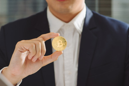 Golden Bitcoin in a Businessman hand, Digitall symbol of a new virtual currency Stok Fotoğraf