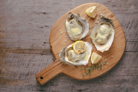 Opened oysters and lemon on wooden board.
