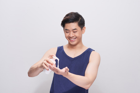 Handsome man pouring washing foam on his hand. 免版税图像