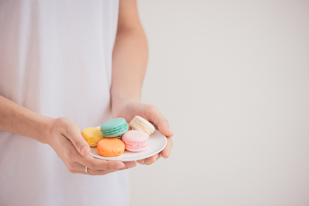 Hands holding colorful pastel cake macarons or macaroons 写真素材 - 100061976