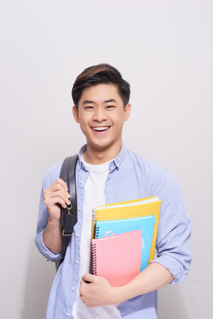 Confident asian handsome student holding books
