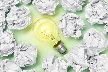 great concept with crumpled office paper and light bulb standing on the table Banco de Imagens