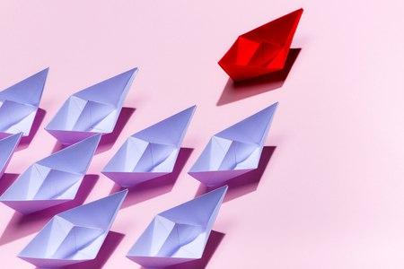 Leadership concept. Red paper ship leading among white Standard-Bild