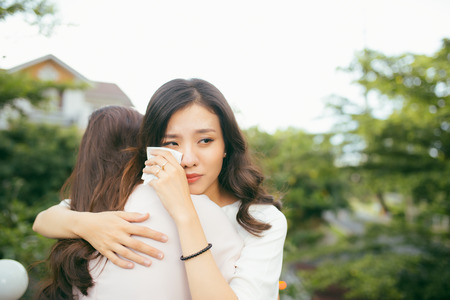 Friendship help support. Depressed asian woman embracing her friend. Archivio Fotografico - 100062457