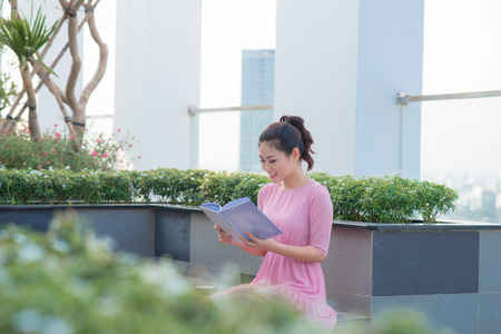 Young Asian executive woman standing and hold folder outside office building, beautiful asian business woman read the document folder outdoor. Stock Photo