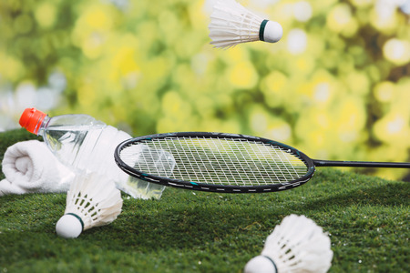 Shuttlecock and badminton racket with water and towel on the grass in the park. Stok Fotoğraf