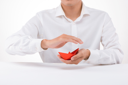 Red paper boat in male hand on white background