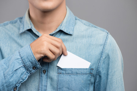 Young man who takes out blank business card from the pocket of his shirt Banque d'images - 100063087