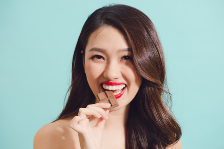 Attractive young asian woman eating chocolate, closeup Stockfoto
