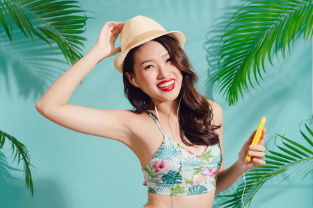 Pretty smiling asian woman enjoys good music in earphones standing over blue background