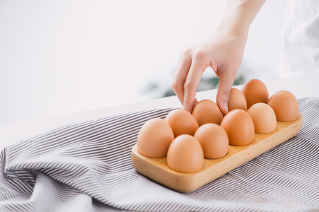 Raw chicken eggs in egg box on table.