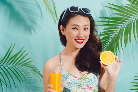 Moda mujer bonita asiática con taza de jugo sobre fondo azul colorido