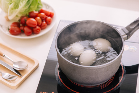 Three eggs boiling in pan of water Stockfoto