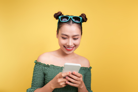 Portrait of a cheerful cute woman using smartphone isolated over yellow background