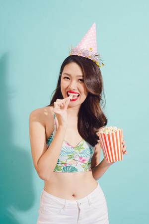 Fashion asian woman drinks coke bottle over blue background.