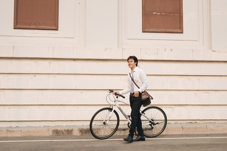 Outdoor portrait of handsome young man with fixed gear bicycle in the street. Imagens