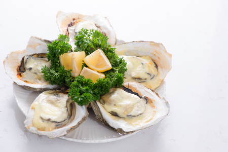 Opened oysters, ice and lemon on wooden board over stone table. Half dozen. With copy space