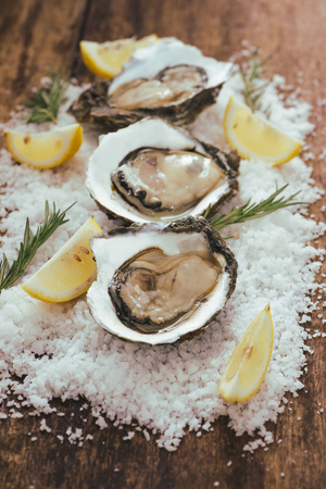 fresh just opened oysters and slice of lemon on rustic wooden background