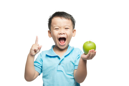 Asian baby boy holding and eating red apple, isolated on white Stockfoto