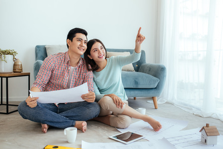 Happy asian couple looking at construction house plan
