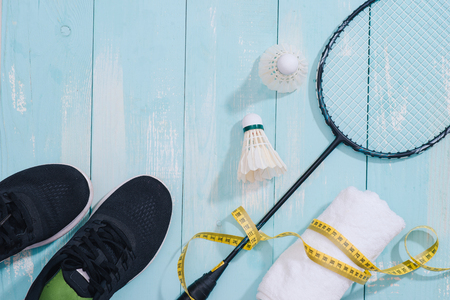 Top view of sport equipments, clock, tape measure, shoes, water bottle, towel, badminton racket and shuttlecock, Healthy lifestyle and fitness concept