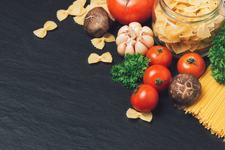 Italian food concept. Pasta ingredients. Cherry-tomatoes, spaghetti pasta, rosemary and spices