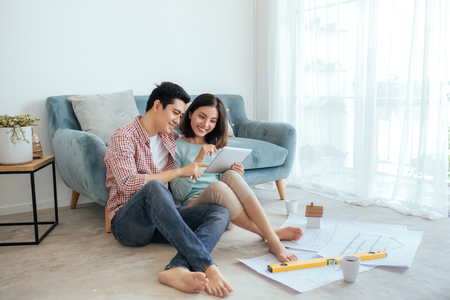 Attractive young asian adult couple looking at house plans. 스톡 콘텐츠