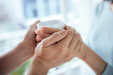 Peaceful asian young couple relaxing at home with cup of tea Stock Photo