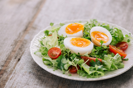 High Angle View of a Nutritious Vegetable Salad with Boiled Egg Slices, Served on a White Plate on Top of a Wooden Table Reklamní fotografie