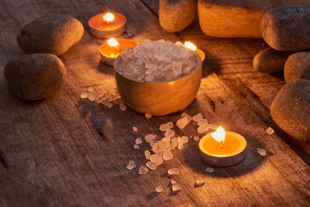 Spa accessories. Sprigs of a Christmas tree, many multi-colored pieces of soap, many different shapes of bottles for a bathroom. Body scrub. Light brick and white wooden as a background