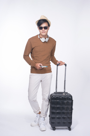 Full length of young tourist asian man holding passport with suitcase over grey background 版權商用圖片
