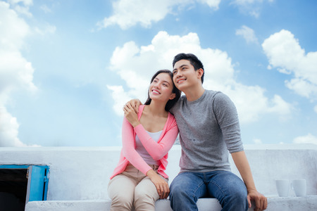Young beautiful woman and asian man laugh against the dark blue sky with clouds