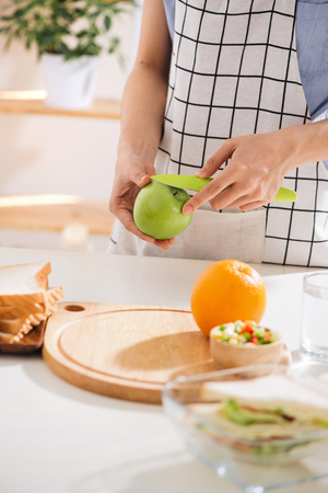 Hands of a woman is making school lunch box in the red color. It is more interesting for children. Caucasian female preparing food (fruits and vegetables) for healthy eating child (kid).