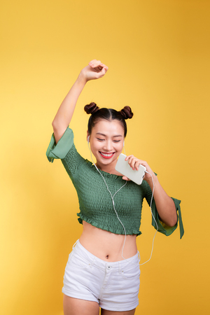 Colorful studio portrait of happy young asian woman with earphones is dancing and singing.