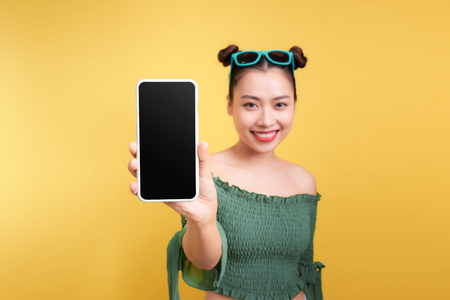Portrait of a cheerful cute woman showing blank smartphone screen isolated over yellow background 스톡 콘텐츠