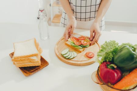 Frauenschürze, die ein Frühstück in der Küche vorbereitet