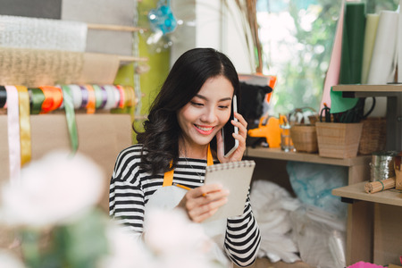 Asian female florist calling on smartphone and making notes at flower shop counter Stock Photo