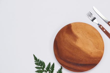 Empty wooden dish with knife and fork on white background, Top view Stockfoto